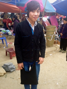 Hmong teenage boy dressed for market. Wearing a contrasting floral lined black jacket and bag.